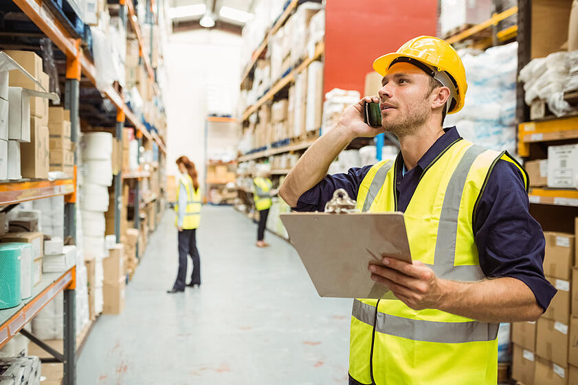 Warehouse-worker-on-phone-holding-clipboard